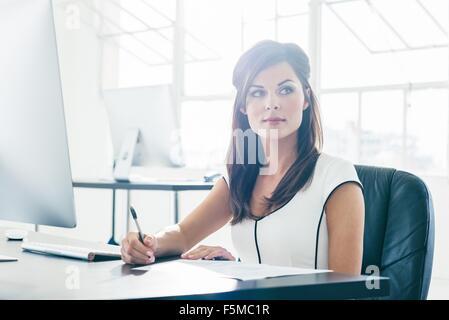 Geschäftsfrau, die Arbeiten am Computer durch Bürofenster - Stockfoto