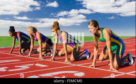 Vier weibliche Athleten auf die Leichtathletik zu verfolgen, kurz vor dem start Rennen - Stockfoto