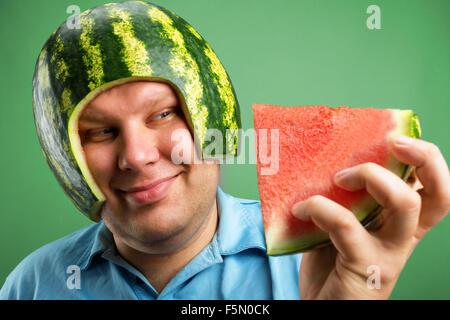 Bizarre Mann in einen Helm aus einer Wassermelone zu essen vorbereiten - Stockfoto