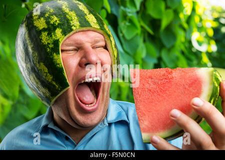 Bizarre Mann in eine Kappe aus einer Wassermelone essen im freien - Stockfoto