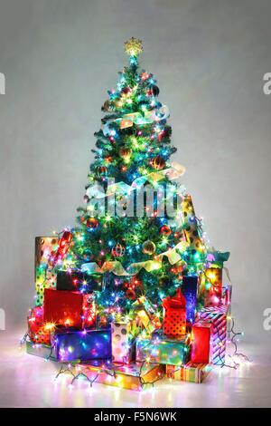 Geschmückter Weihnachtsbaum mit bunten Lichtern umgeben von präsentiert. - Stockfoto