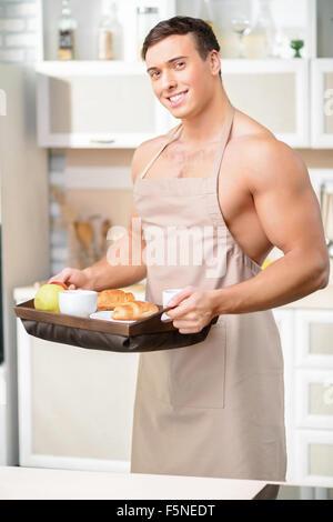 Junger attraktiver Mann mit einem Tablett für das Frühstück. - Stockfoto