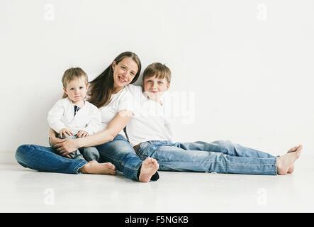 Familie Mutter mit Kindern Studio Portrait voller Länge sitzen in Jeans auf weißem Hintergrund
