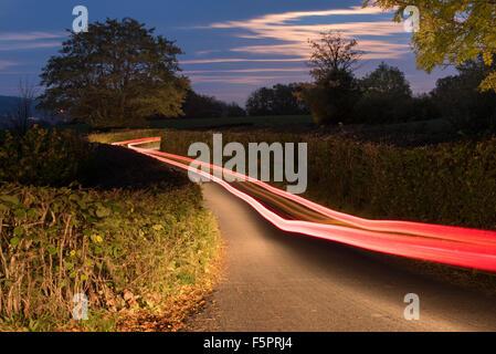 Lichtspuren aus einem Auto unterwegs entlang einer Landstraße in der Nacht, mit einer langen Verschlusszeit für eine Langzeitbelichtung