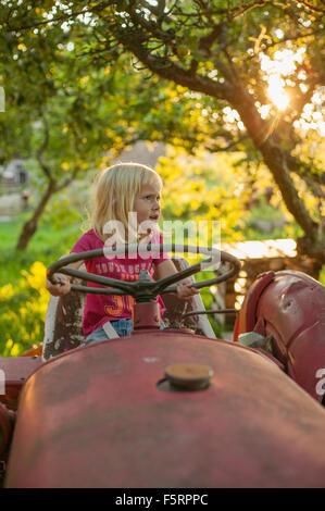 Schweden, Skane, Osterlen, Mädchen (4-5) am Traktor