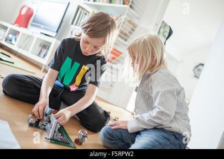 Schweden, Vastergotland, Lerum, Geschwister (6-7, 8-9) mit Kunststoffblöcke spielen - Stockfoto