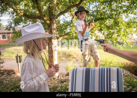 Schweden, Smaland, Anderstorp, Mama spielt mit ihren Kindern (8-9, 10-11) im hinteren Hof - Stockfoto