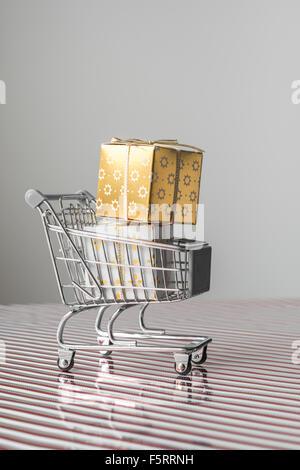 Mini Trolley mit Weihnachtsgeschenk auf Xmas Streifen - Stockfoto