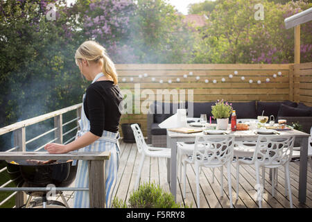Schweden, Vastergotland, Lerum, Reife Frau Kochen auf Terrasse - Stockfoto