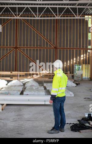 Schweden, Bohuslan, kantiger, Mann im Bauarbeiterhelm Blick auf Baustelle - Stockfoto
