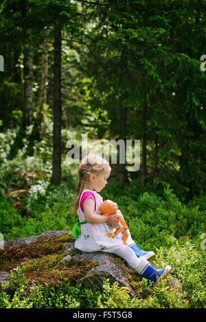 Finnland, Paijat-Hame, Seitenansicht der Mädchen (2-3) mit Puppe auf Felsen sitzend - Stockfoto