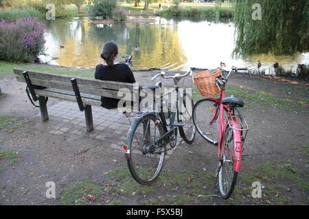 Junge Frau saß auf einer Parkbank mit klassischen alte Fahrräder und Teich - Stockfoto