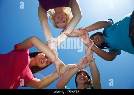 Vier Freundinnen halten einander an den Handgelenken - Stockfoto