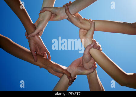 Vier Menschen halten einander an den Handgelenken - Stockfoto