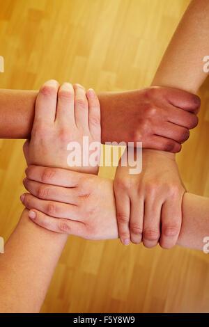 Vier Hände halten einander an den Handgelenken - Stockfoto