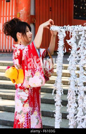 Seitenansicht des jungen japanischen Frau in Rot kinomo bis omikuji zu binden, ein Papier fortune Slip zu Rahmen - Stockfoto