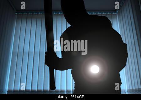 Einbrecher oder Eindringling innerhalb eines Hauses oder Büros mit Taschenlampe und Baseball Schläger - Stockfoto
