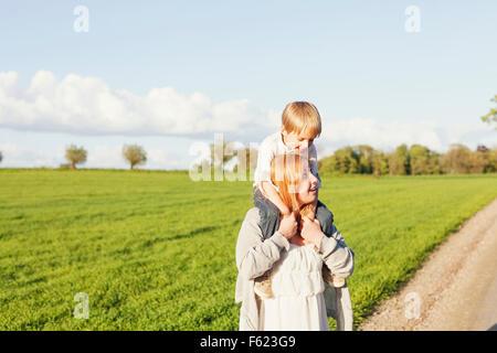 Schwangere Frau mit Sohn auf Schultern bei Wiese gegen Himmel - Stockfoto