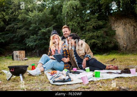 Lächelnd Freunde mit digital-Tablette zusammen beim Picknick im Wald - Stockfoto
