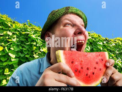 Bizarre Mann isst Wassermelone im Freien im Sommer - Stockfoto