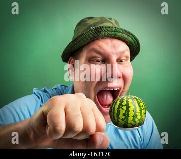 Bizarre Mann bereitet sich auf Löffel kleine Wassermelone essen - Stockfoto