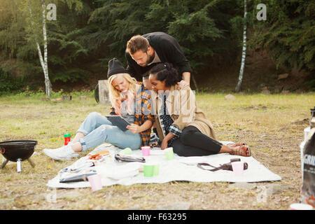 Multi-ethnischen Freunde mit digital-Tablette zusammen im Wald - Stockfoto