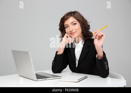 Junge lockig lächelnd gerne hübsche Frau arbeiten mit Laptop und schreiben in Notebook - Stockfoto