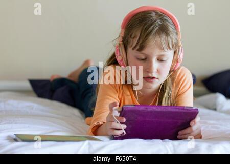 Mädchen arbeiten an iPad Mini mit rosa Kopfhörer - Stockfoto