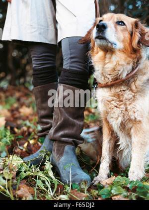 Nahaufnahme von Frau trägt Stiefel stehend mit Hund - Stockfoto