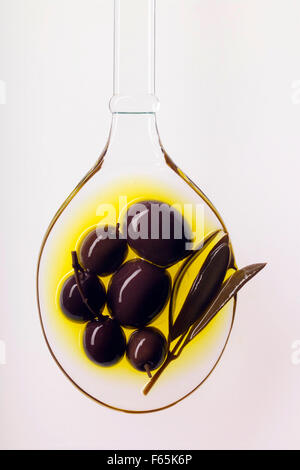 schwarze Oliven in Löffel Öl - Stockfoto