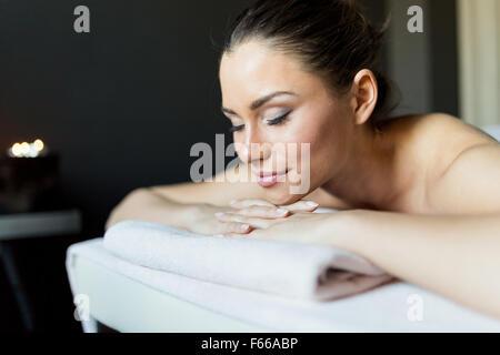Porträt einer jungen und schönen Frau mit geschlossenen Augen auf einer Massageliege in einem dunklen Raum bei Kerzenschein - Stockfoto