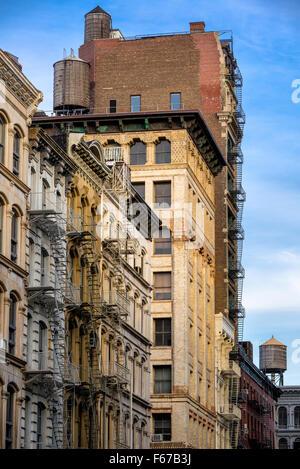 Soho Loft-Gebäude mit Feuerleiter und Wassertürme in Broome Street, Manhattan, New York City. - Stockfoto