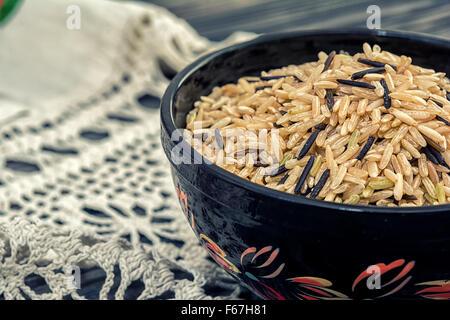 Ungeschälter brauner und schwarzer Reis in Holzschale auf hölzernen Hintergrund mit rustikalen Deckchen häkeln - Stockfoto