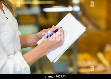 Frau Überprüfung Liste im Supermarkt - Stockfoto