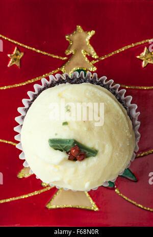 Christmas Pudding Red Velvet Muffin auf Weihnachtsteller mit gold Baum und Sterne - Stockfoto