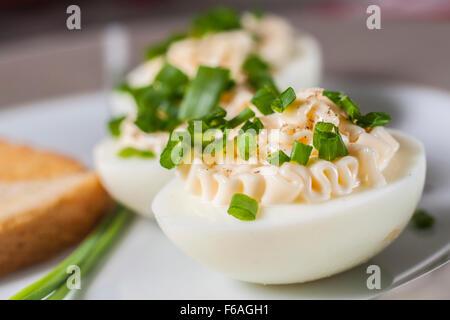 Nahaufnahme, gekochte Eier mit Mayonnaise und geschnittenen Schnittlauch auf Platte - Stockfoto