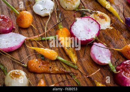 frische Baby-Karotten und Radieschen geröstet und gewürzt mit Öl und Gewürzen - Stockfoto