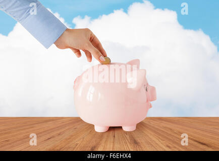 Nahaufnahme von Hand, Münze ins Sparschwein - Stockfoto