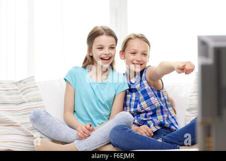 zwei glückliche kleine Mädchen zu Hause vor dem Fernseher - Stockfoto
