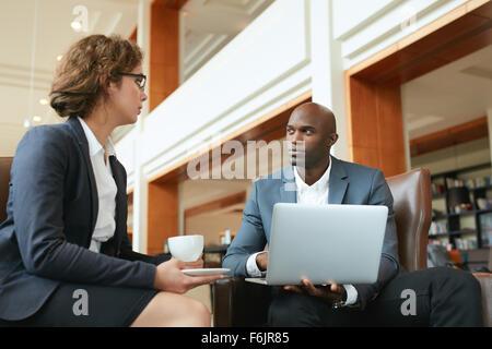 Zwei Geschäftsleute treffen im Café. Geschäftsmann mit Laptop und Geschäftsfrau Kaffeetrinken während der Arbeit - Stockfoto
