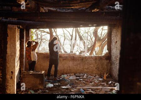 Rückansicht von Mann und Frau aus verlassenen Gebäude fotografieren - Stockfoto