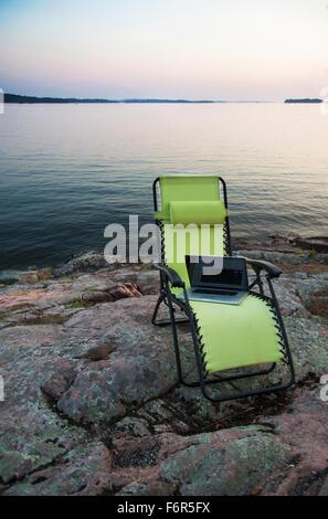 Laptop auf Liegestuhl in der Nähe von abgelegenen Fluss - Stockfoto