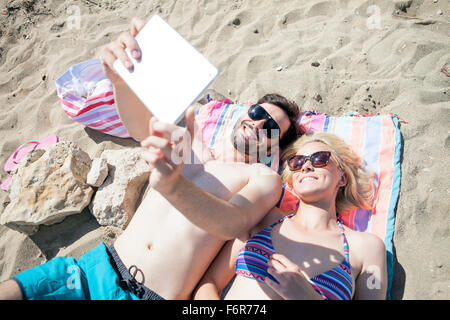 Junges Paar mit digital-Tablette am Strand - Stockfoto