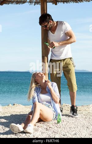 Junger Mann gießt Wasser auf Freundin am Strand - Stockfoto
