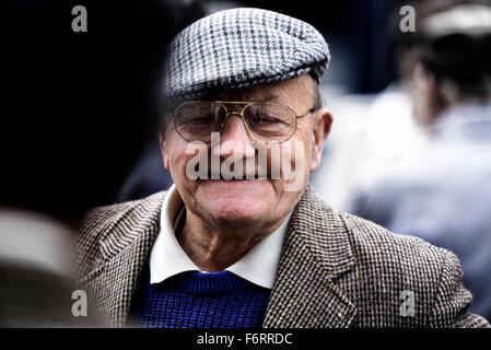Ein Lächeln auf den Lippen alte Herr ein Tweed Tuch Mütze und Jacke - Stockfoto
