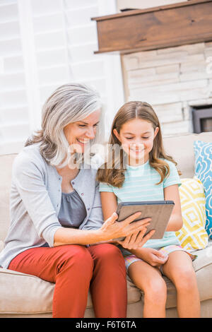 Kaukasische Großmutter und Enkelin mit digital-Tablette auf sofa - Stockfoto