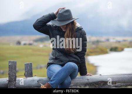 Kaukasische Frau sitzt am ländlichen river - Stockfoto