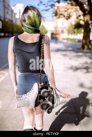 Spanien, Gijon, Rückansicht der jungen Frau mit grün gefärbte Haare mit Inline-Skates über Schulter - Stockfoto