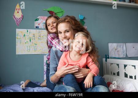 Porträt der Frau mit ihren kleinen Töchtern im Kinderzimmer - Stockfoto