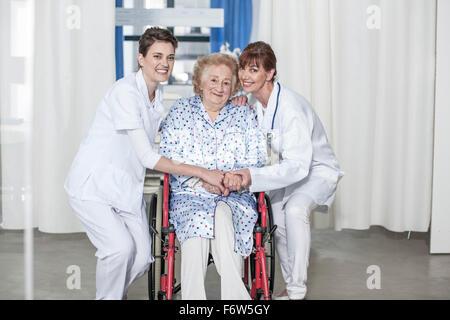 Arzt und Krankenschwester Pflege für ältere Patienten im Rollstuhl - Stockfoto